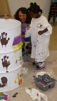 Artist Susan Rosano and a youth participant work together on oil drum art.
